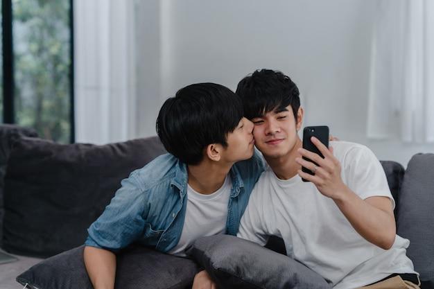 Азиатский влияющий гей-пара влог дома. азиатские люди lgbtq счастливые ослабляют потеху используя видео ролика образа жизни записи мобильного телефона технологии загружают в социальные медиа пока лежа софа в живущей комнате.