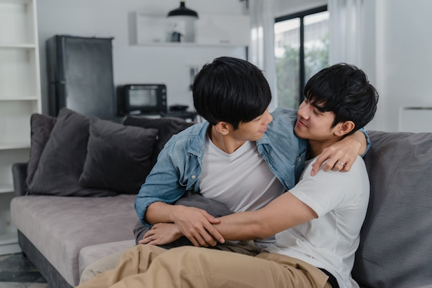 若いアジア同性愛者のカップルが抱擁し、自宅でキスします。魅力的なアジアのlgbtqの誇り男性はリラックスして、リビングルームでソファに横たわっている間一緒にロマンチックな時間を過ごします。
