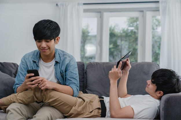 現代の家で携帯電話とタブレットを使用して若いゲイlgbtqカップル。アジアの恋人男性幸せなリラックスした笑いと楽しい技術は、リビングルームでソファに横たわっている間一緒にインターネットでゲームをプレイします。