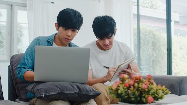 Компьтер-книжка молодых азиатских пар гомосексуалиста работая на современном доме. азия lgbtq + мужчины счастливы расслабиться, весело используя компьютер и анализируя свои финансы в интернете вместе, лежа на диване в гостиной дома.