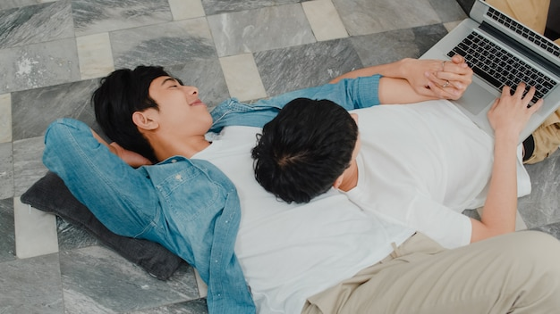 現代の家でコンピューターのラップトップを使用して若い同性愛者のカップル。アジアのlgbtqの男性は、家のリビングルームの床に横たわっている間、一緒にインターネットで映画を見る技術を使用して楽しいリラックスを楽しんでいます。