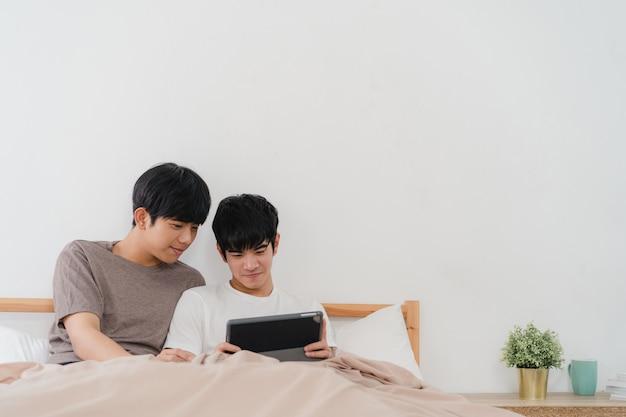 Азиатские пары гомосексуалиста используя таблетку дома. молодые азиатские lgbtq + мужчины счастливы расслабиться вместе отдохнуть после пробуждения, проверки почты и социальных сетей, лежа на кровати в спальне дома утром.