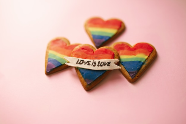 愛はピンクの壁にlgtbハートクッキーが大好きです。レインボーハートクッキー。心のlgbtとサイン虹色のストライプ。