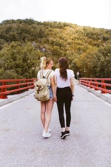 山の近くの道路上のバックパックと恋に若いガールフレンドの背面図。手を繋いでいるカップル。 lgtb旅行と冒険のコンセプト。森の真ん中にいる旅行者。