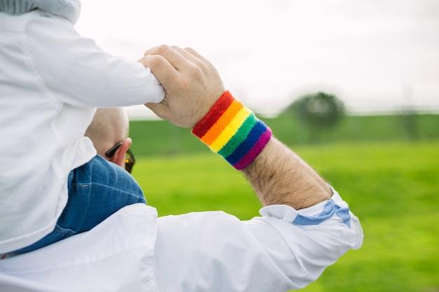ゲイのプライドレインボーフラグリストバンドを身に着け、養子を公園で運ぶ成人男性。 lgtbと平等の概念