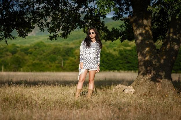 リバティの安心コンセプト。魅力的な若い女性がフィールドを歩いています。彼女は微笑みながら楽しみにしています。
