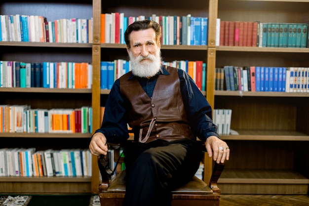 図書館で椅子に座っている暗いシャツとズボンと革のベストを身に着けている教員の司書、背景の書棚。知識、学習、教育のコンセプト