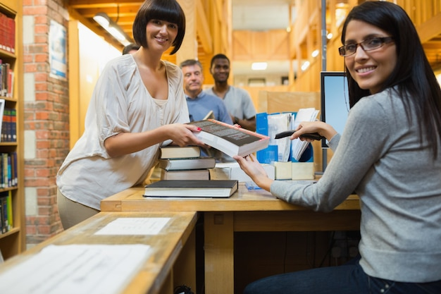 Librarian scanning book and handing to woman