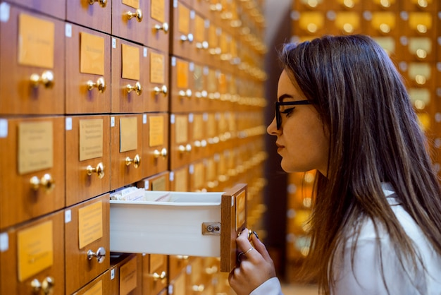 Library or archive reference card catalog. student girl trying to find necessary book using library paper database
