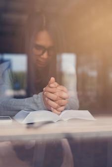 Library図書館で聖書を読んでいる間に祈っている美しい女性