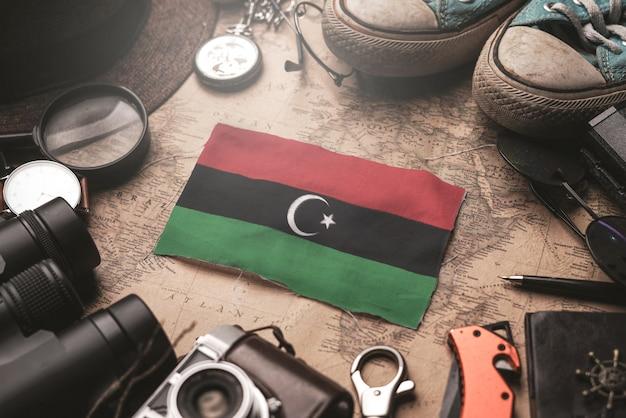 Флаг ливии между аксессуарами путешественника на старой винтажной карте. концепция туристического направления.