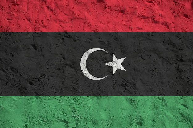 Флаг ливии изображен яркими красками на старой рельефной штукатурке стены. текстурированный баннер на грубом фоне