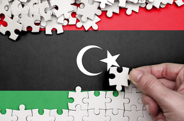 Libya flag is depicted on a table on which the human hand folds a puzzle of white color