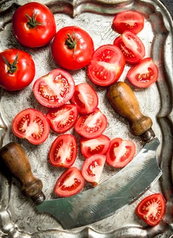Liced tomatoes on a steel tray.