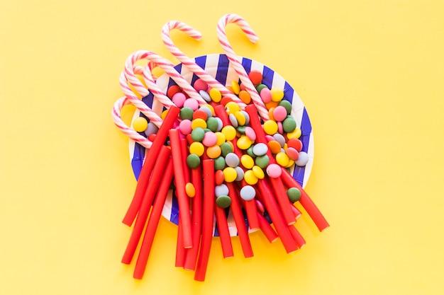 노란색 배경 위에 접시에 감초, 보석 및 크리스마스 지팡이 사탕