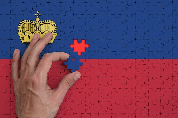 Liechtenstein flag  is depicted on a puzzle, which the man's hand completes to fold