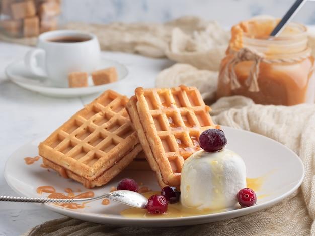 Льеж вафли с карамелью, ягодами и мороженым. домашние вафли с вкусным карамельным соусом на тарелку.