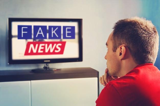テレビ宣伝の主流メディアの偽情報の嘘、偽のニュースレポート。視聴者はテレビを見ていて、偽のニュースを信じていません。男はテレビで嘘を見ないように目を閉じます。