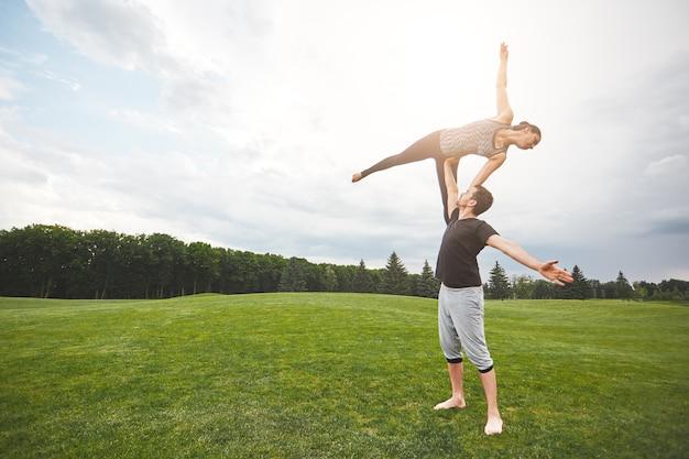 생활 균형 활동적인 스포티 한 부부는 자연 속에서 아크로 요가를 하는 강한 남자에 서 있습니다.