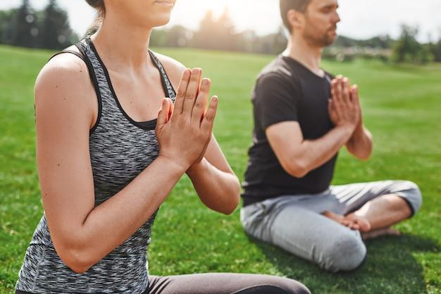 로터스 포즈에 앉아있는 동안 야외에서 명상하는 젊은 부부의 삶의 균형 근접 촬영