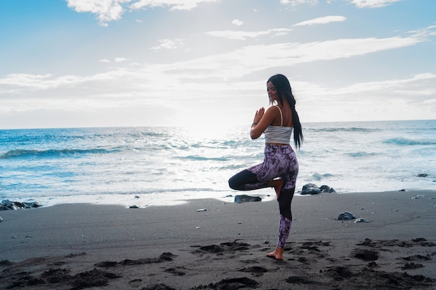 Life balance. full length of slim sporty woman in sports wear doing tree pose or vrikshasana while practicing yoga and meditation on seashore in peaceful morning, rear view. healthy lifestyle concept
