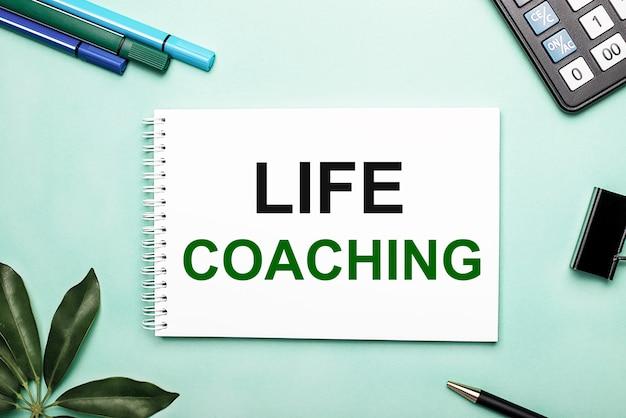 Life coachingは、文房具とシェフラーシートの近くの青い背景の白いシートに書かれています。アクションの呼び出し。動機付けの概念