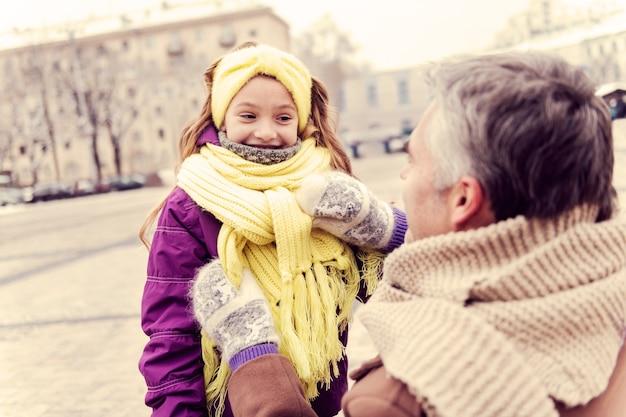 삶의 즐거움. 그녀의 아빠를 보면서 긍정을 표현하는 아름다운 아이