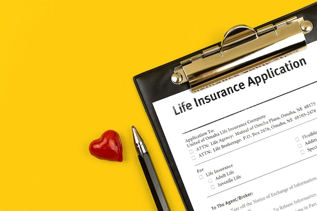 생명보험 신청. 노란색 바탕 화면에 계약, 펜 및 붉은 마음이 있는 클립보드. 상위 뷰 사진