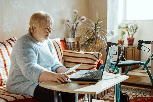 ノートパソコンとメガネで高齢者の成熟した女性のための生命保険障害医療保険契約