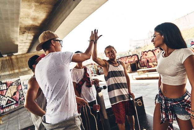 2人の若い現代人の周りの友達が屋外でスケートの友達とぶらぶらしながらハイタッチをしているときの人生は素晴らしいです