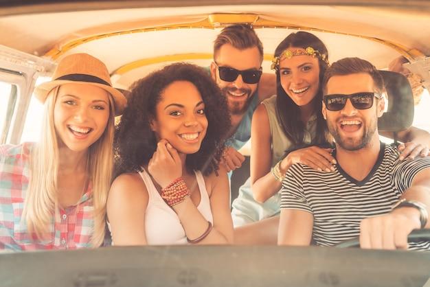 Жизнь лучше, когда рядом друзья. группа радостных молодых людей улыбаются в камеру, сидя в минивэне вместе