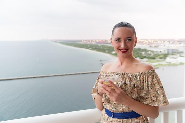 Жизнь хороша. сексуальная женщина на балконе с видом на море. взгляд красоты красивой женщины. чувственная женщина держит напиток. сексуальная женщина отдыхает в отеле. летний отпуск. путешествия и страсть к путешествиям. курорт.