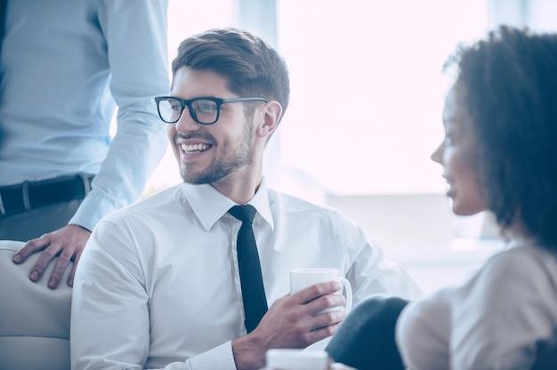 Жизнь бизнесмена. крупным планом молодой красивый веселый мужчина держит чашку кофе и смотрит в сторону с улыбкой, сидя в офисе со своими коллегами
