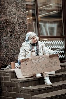 이민자의 삶. 이 나라에서 이민을하면서 계단에 앉아있는 쾌활한 노인 여성