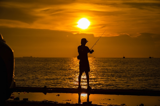 Life portrait fishermen silhouette on the sea and the sunset over background evening time