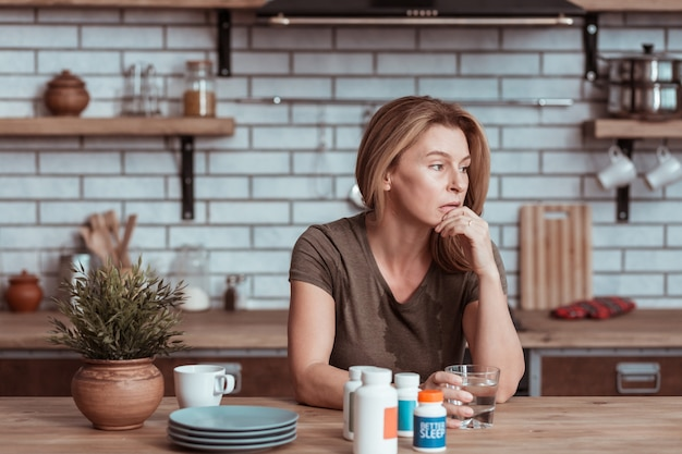 Life problems. depressed woman sitting in kitchen while taking pills and thinking about life problems