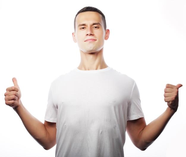 ライフスタイルと人々のコンセプト:両手を空中に上げたシャツを着たカジュアルな若い男。勝者と幸せ。