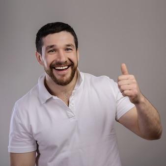 ライフスタイルと人々の概念:孤立した背景の上に親指を示す白いtシャツを着て幸せなハンサムな男。