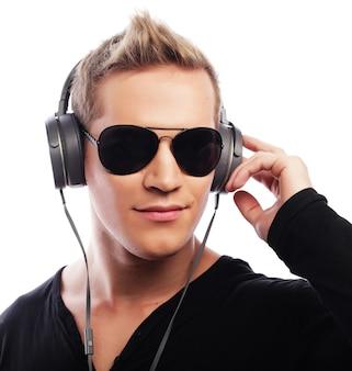 Концепция образа жизни и людей: счастливый молодой человек, слушающий музыку в наушниках