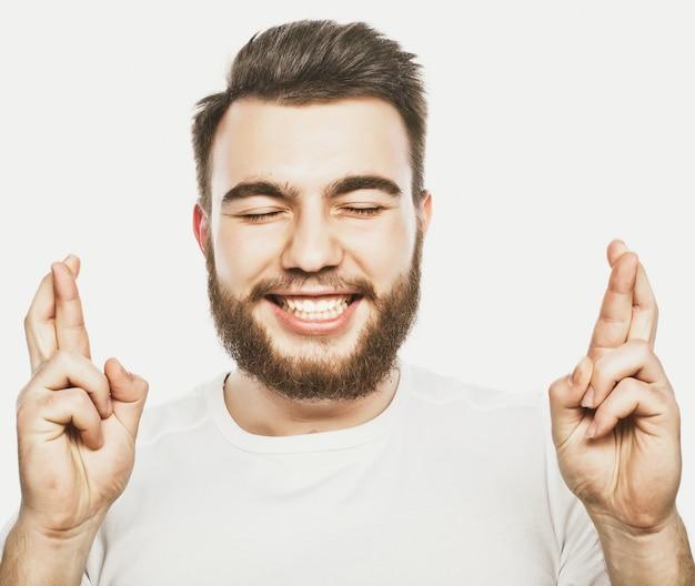 Концепция образа жизни и людей: ожидание особого момента. портрет молодого бородатого человека в рубашке, держа пальцы, стоя против белого пространства. хипстерский стиль и положительные эмоции.