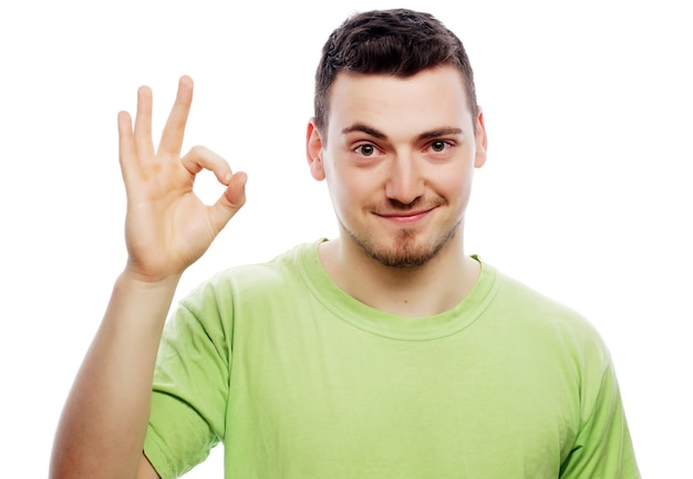 ライフ スタイルと人々 のコンセプト: ポケットに手を入れてカメラに微笑みながら勝利のジェスチャーを示すカジュアルな若者。白い背景に分離
