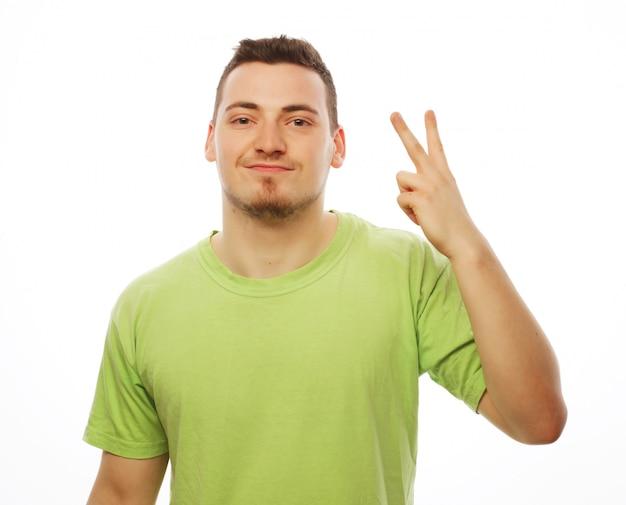 ライフスタイルと人々の概念:彼のポケットに手でカメラに微笑んでいる間勝利のジェスチャーを示すカジュアルな若者。ホワイトスペースに分離