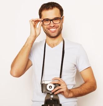 라이프 스타일과 사람 개념:흰색 바탕에 복고풍 카메라를 든 젊은 남자