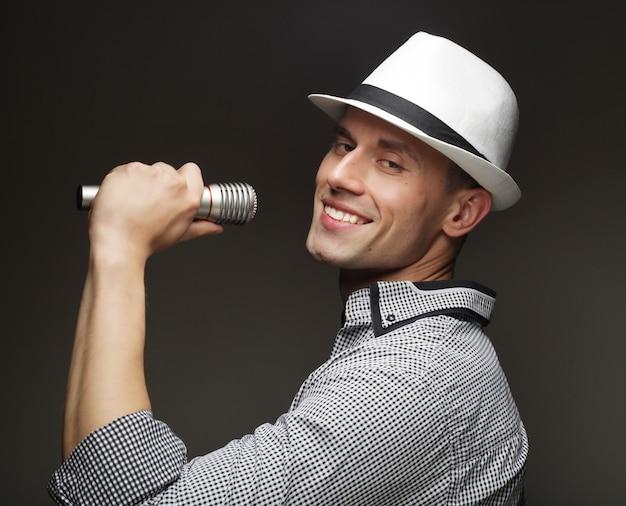 라이프 스타일과 사람 개념:마이크를 가진 젊은 가수 남자