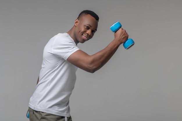 Стиль жизни. привлекательный радостный черный мускулистый мужчина с голубыми гантелями занимается спортом в студии
