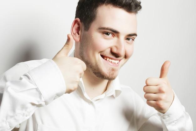 Концепция образа жизни, бизнеса и людей: деловой человек, идущий большими пальцами руки вверх, изолированный на белом