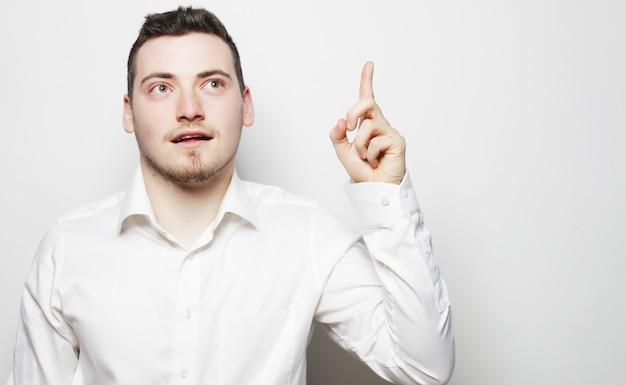 Образ жизни, бизнес и люди концепции: деловой человек указывая пальцем вверх. изолированный на пустом пространстве /
