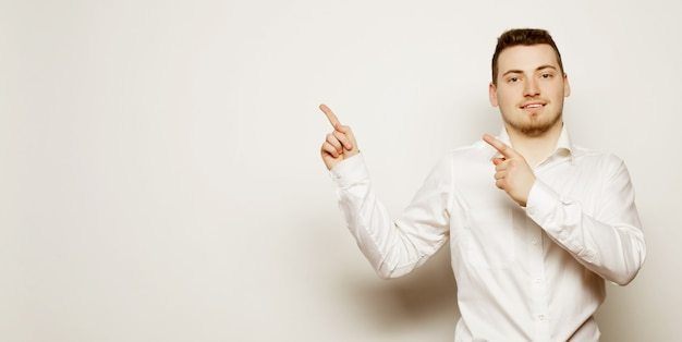 ライフスタイル、ビジネス、人々の概念:ビジネスマンは白い背景の上に右側の指で指しています。