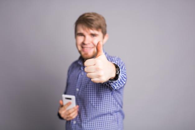 Образ жизни, бизнес и люди концепции - случайный молодой человек показывает палец вверх знак и держит телефон
