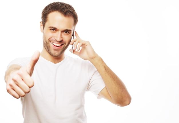 Образ жизни, бизнес и люди концепции: случайный молодой человек показывает палец вверх знак, разговаривая по телефону и улыбаясь в камеру. изолированные на белом фоне